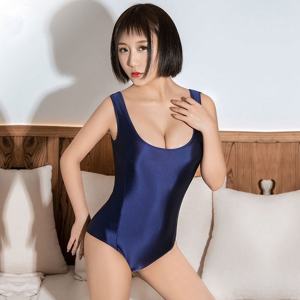 front view of lady wearing a blue color wet look bodysuit feauring a scoop neckline, thick shoulder straps, a zipper closure crotch and a cheeky cut back.
