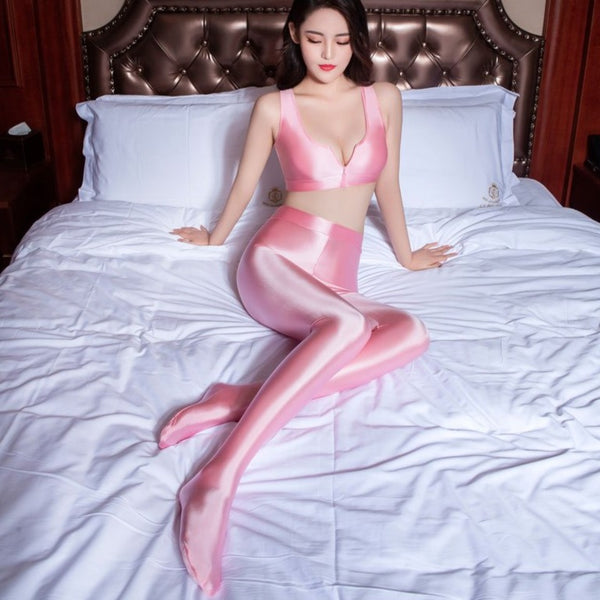 front view of lady wearing pink color top & legging set featuring a top with thick spaghetti straps, and front zipper closure, and pair with a matching over the toe legging with elastic waistband.