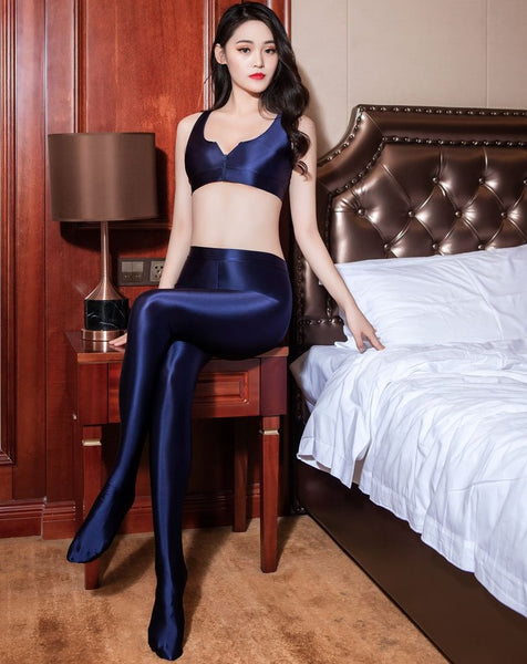 front view of lady wearing blue color top & legging set featuring a top with thick spaghetti straps, and front zipper closure, and pair with a matching over the toe legging with elastic waistband.