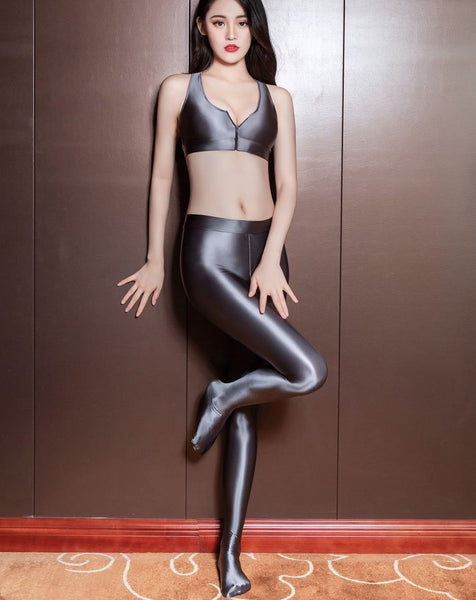 front view of lady wearing grey color top & legging set featuring a top with thick spaghetti straps, and front zipper closure, and pair with a matching over the toe legging with elastic waistband.