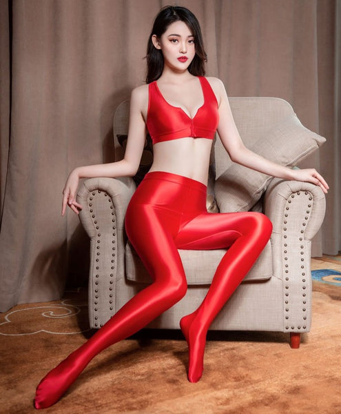 front view of lady wearing red color top & legging set featuring a top with thick spaghetti straps, and front zipper closure, and pair with a matching over the toe legging with elastic waistband.