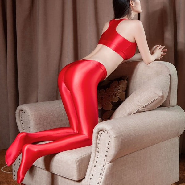 back view of lady wearing red color top & legging set featuring a top with thick spaghetti straps, and front zipper closure, and pair with a matching over the toe legging with elastic waistband.
