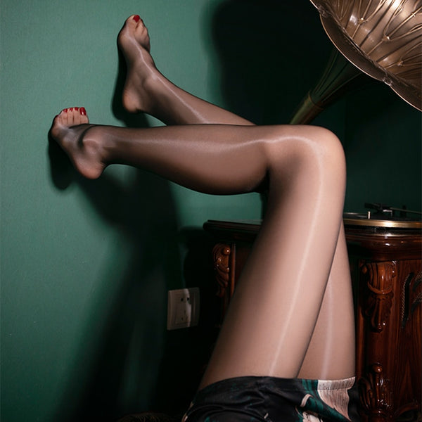 front view of lady wearing black glossy sheer pantyhose with solid wide waist band showing off her feet