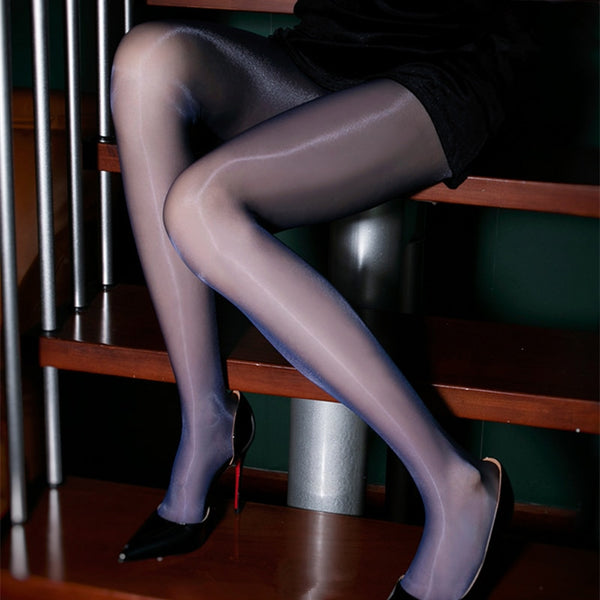 front view of lady wearing blue glossy sheer pantyhose with solid wide waist band wearing black high heels
