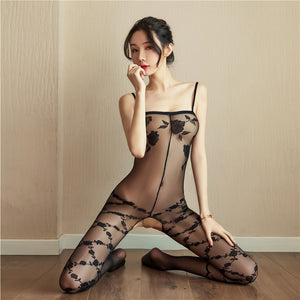 front view of lady wearing a black bodystocking featuring intricate floral design, spaghetti straps, and an open crotch.