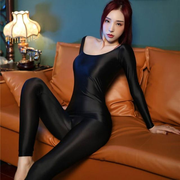 front view of lady wearing black shiny wet look top & legging set featuring a shiny wet look top with off shoulder neck line and long sleeves and a matching legging.
