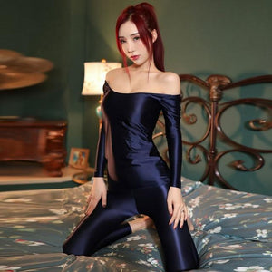 front view of lady wearing dark blue shiny wet look top & legging set featuring a shiny wet look top with off shoulder neck line and long sleeves and a matching legging.