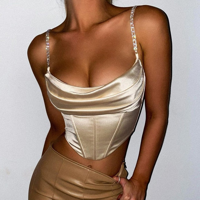 front view of lady wearing beige color corset crop top that shows off your luscious curves featuring adjustable chain link shoulder straps, a scoop neckline, and back zip closure.