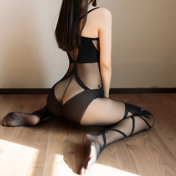 back view of lady wearing a black bodystocking, featuring spaghetti straps, opaque cups, square neckline, criss-cross embroided thigh high stockings, and an open crotch showing off her feet