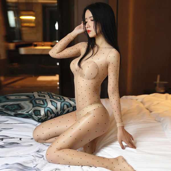 side view of lady wearing beige shiny bodystocking featuring long sleeves, scoop neckline, all round polka dot print, showing off her feet
