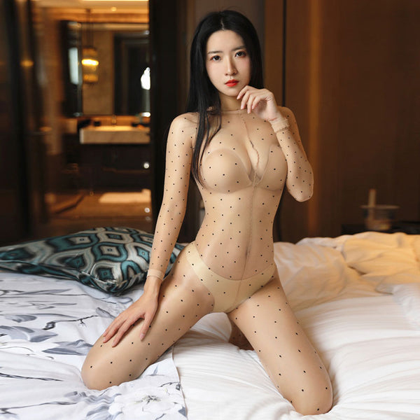 front view of lady wearing beige shiny bodystocking featuring long sleeves, scoop neckline, all round polka dot prints