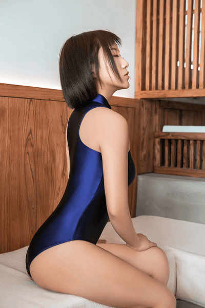 side view of lady wearing a blue wet look bodysuit featuring a high neckline, a front zipper closure, and a cheeky cut back.