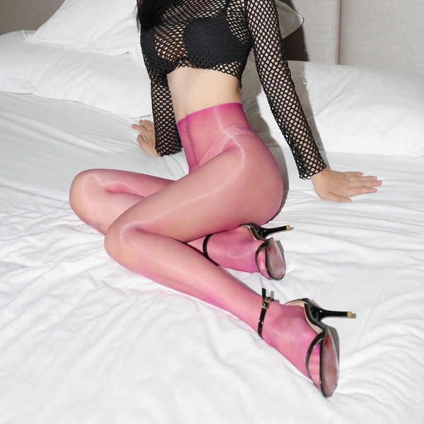 side view of lady wearing fishnet top with black bra with fuchsia crotchless shiny pantyhose with black shiny high heels