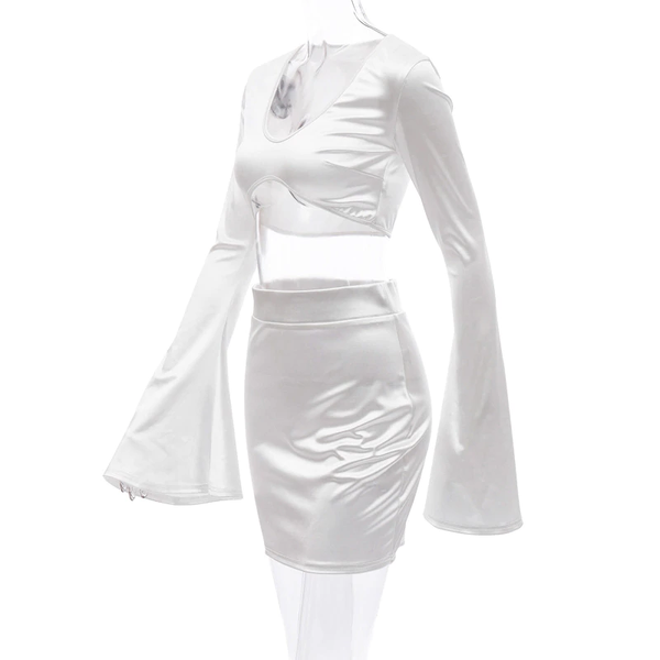 side view of white satin crop top with long sleeves, scoop neckline and a matching mini skirt.
