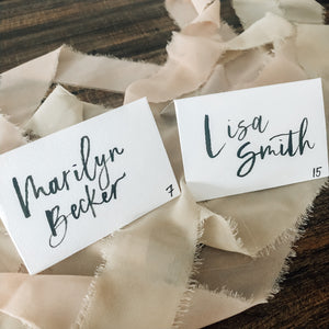 Escort or place card | Brush lettering on white tent