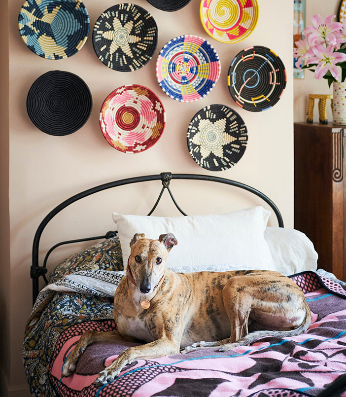 millie on bed with rwandan baskets from artisans & adventurers