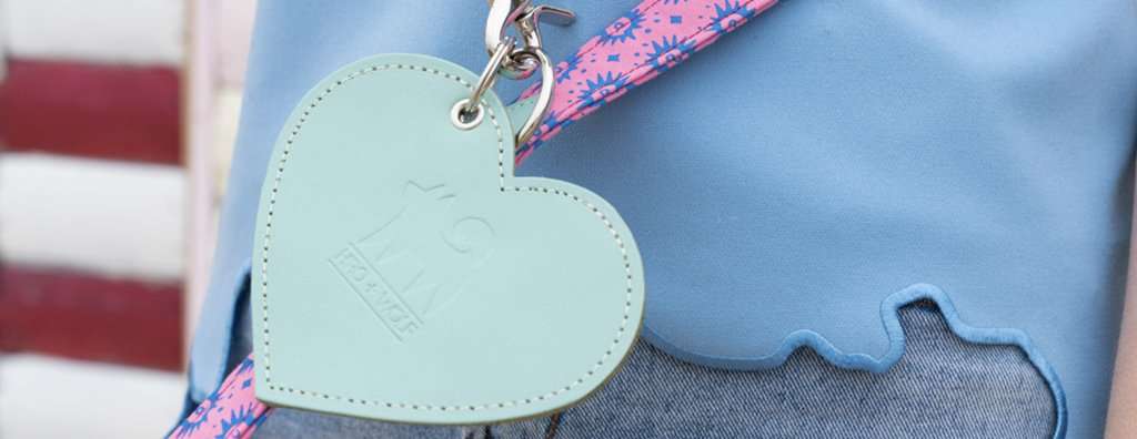 Mint leather heart shaped poo bag holder clipped onto a pink and blue lead