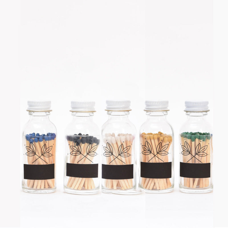 group image of five glass matchstick bottles with colored tips in green, blue, black, white and yellow