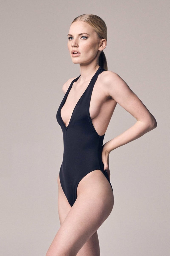 A blonde woman with a ponytail wearing a black PIXIE WON'T PLAY-brand swimsuit