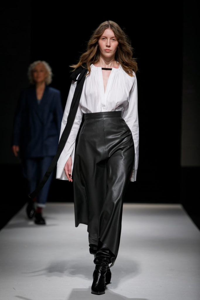 A woman on a walkway wearing a leather skirt and a white shirt
