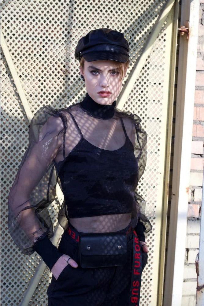 Woman wearing a fishnet, black leather cap and a Furora Subtera leather bag