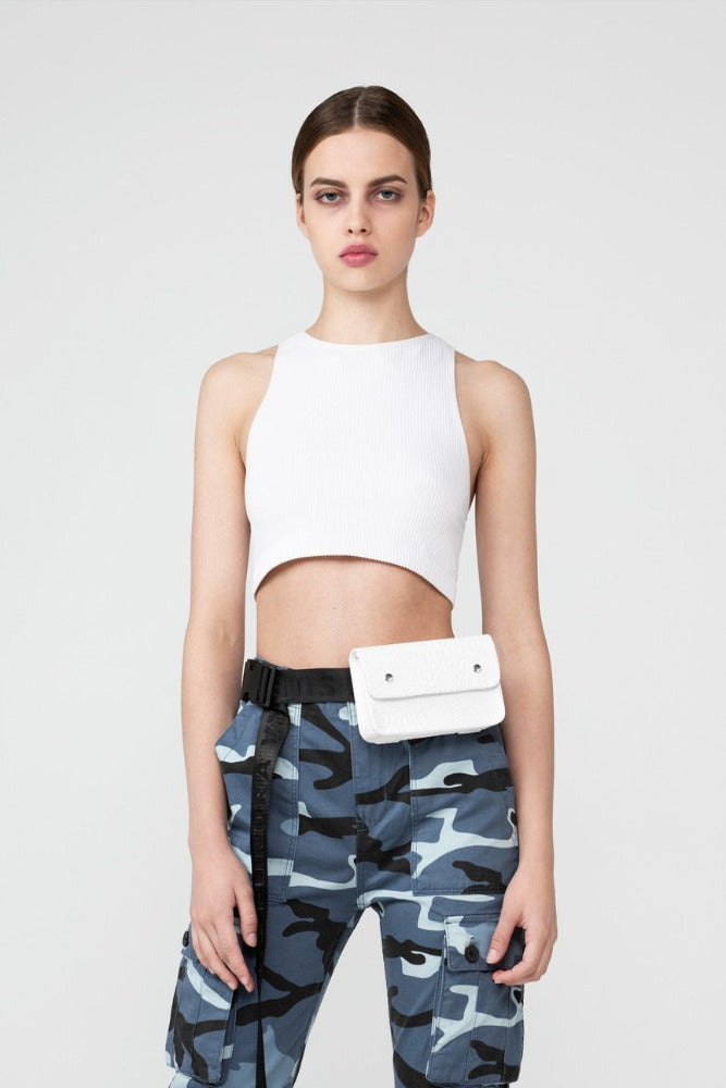 A woman wearing a white tanktop, urban camo pants and a white crocodile Furora Subtera bag on her hips