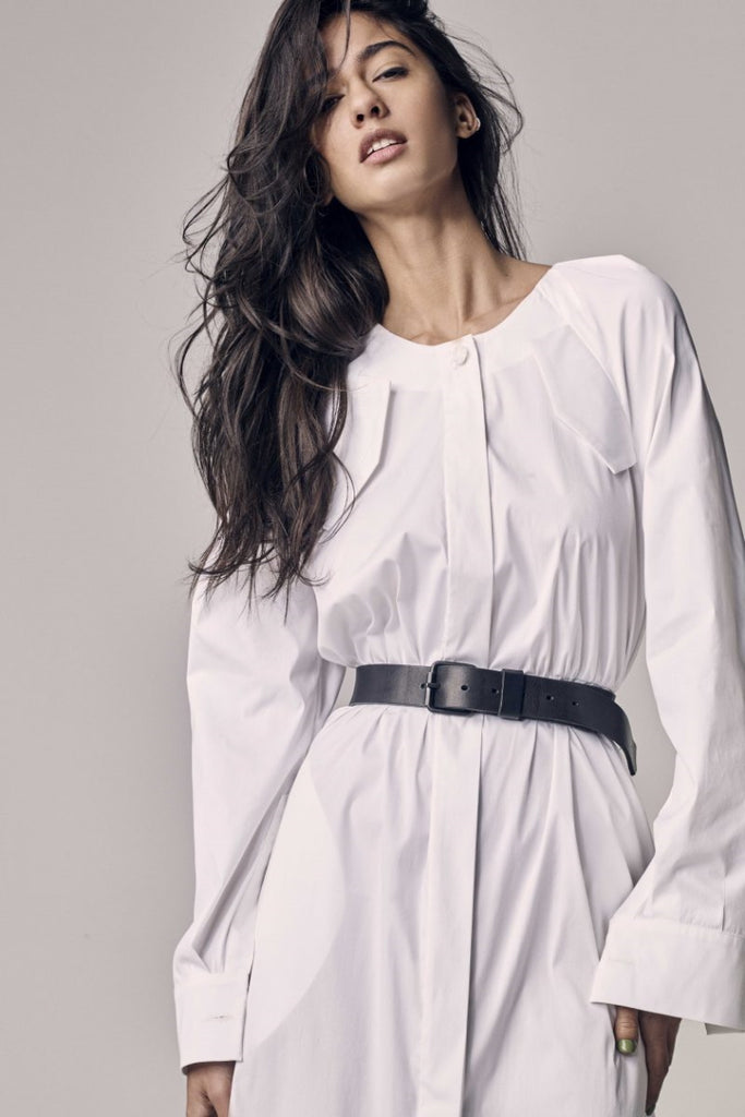 Black-haired woman wearing a white shirt dress with a black belt