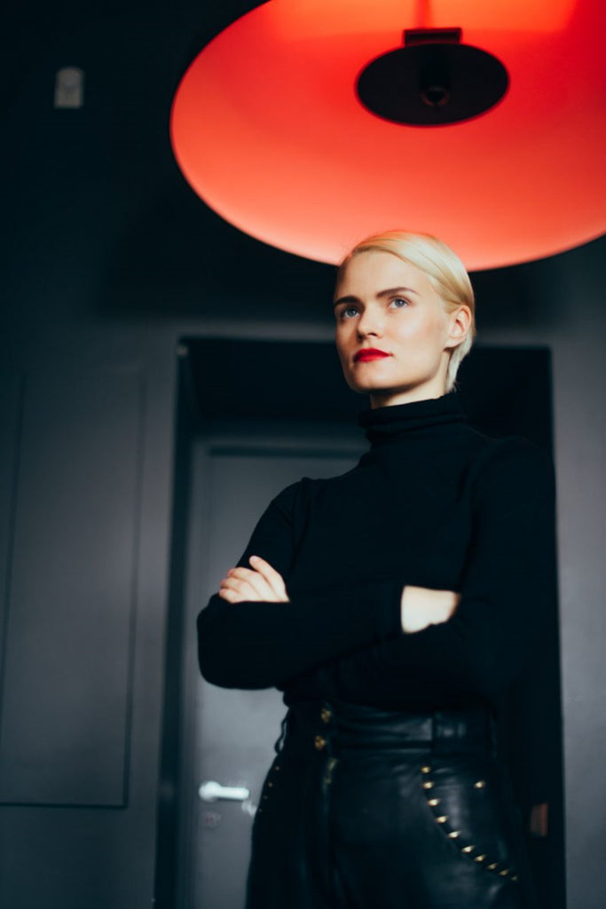 Blonde woman with her arms crossed wearing a black turtleneck and black pants