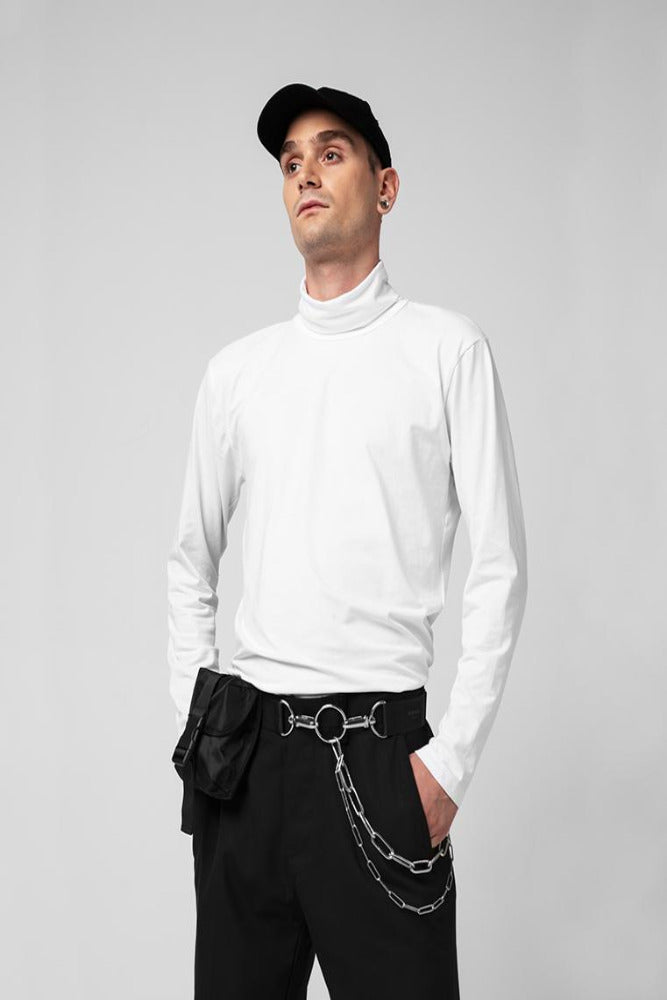 A man in a white sweater and black trousers wearing a chain belt bag