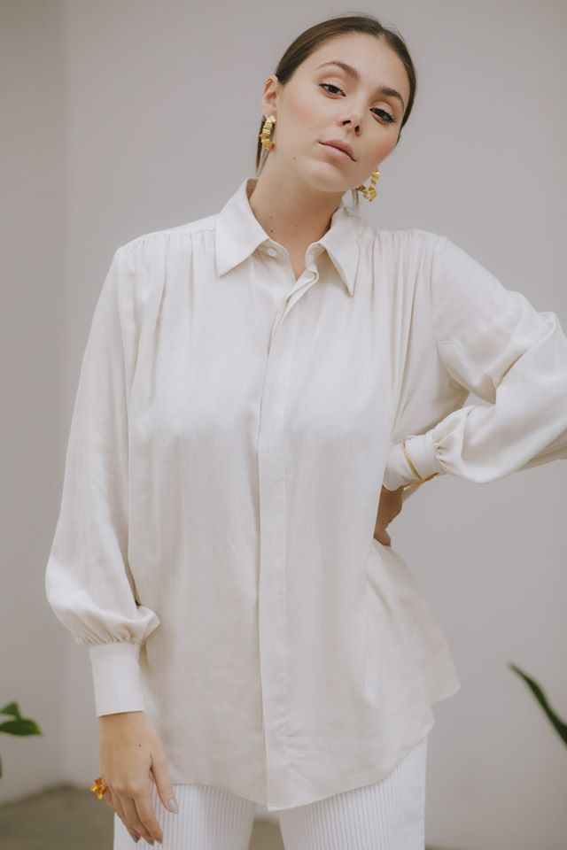 A woman wearing a white blouse made by Urban Studio