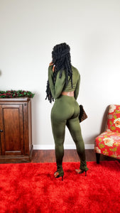 Olive green matching set. Long sleeve (lower in the front and slightly curved on the sides) top with a black front zipper featuring thumb holes/inserts and a mock neck collar when zipped up.  Paired with matching high waist bottoms with adjustable outer ankle zippers. Great stretch.