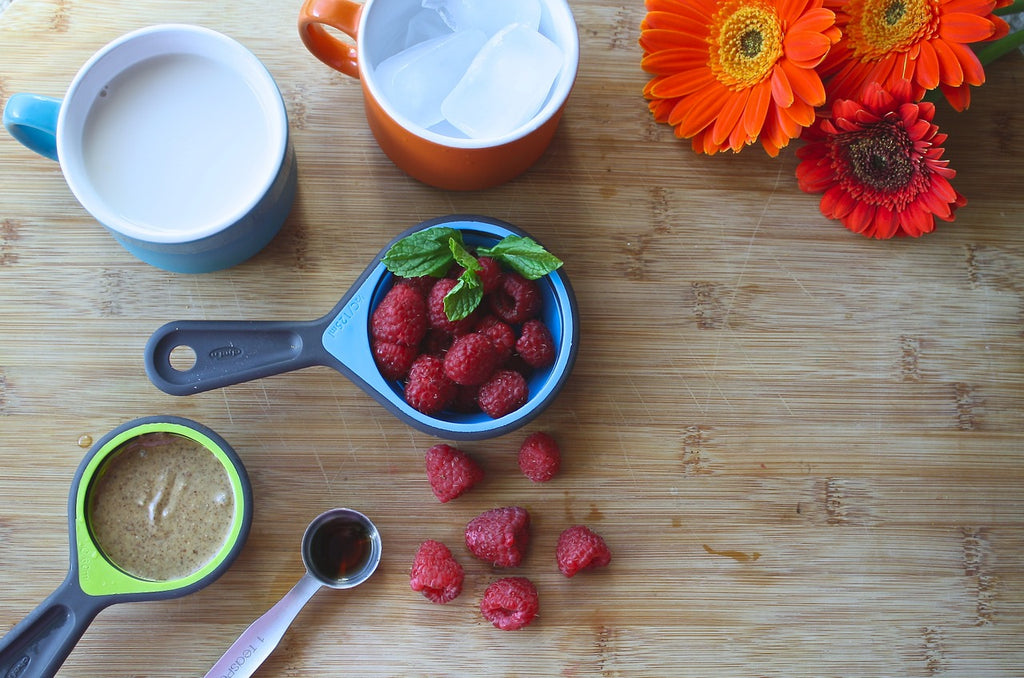 Easy And Healthy Summer Drinks For Kids. On the table are kept a cup of milk, a cup of ice, some strawberries, a tbsp of cocoa, chocolate paste and some flowers