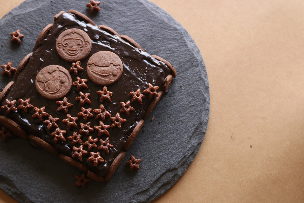 Healthy Recipe Of Ragi Chocolate Cake. A cake kept with topping of puffs and biscuits.
