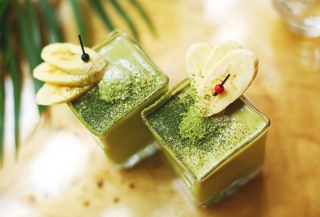 Immune Booster- Kiwi Spinach Banana And Oats Smoothie drink kept in a glass with bananas on the glass sides