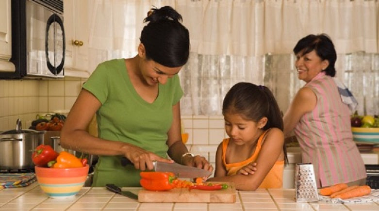 Maintaining health of body and mind, while earning from home! Mother in the kitchen showing her daughter how to cut vegetables while they are happily looked by the their grandmother.