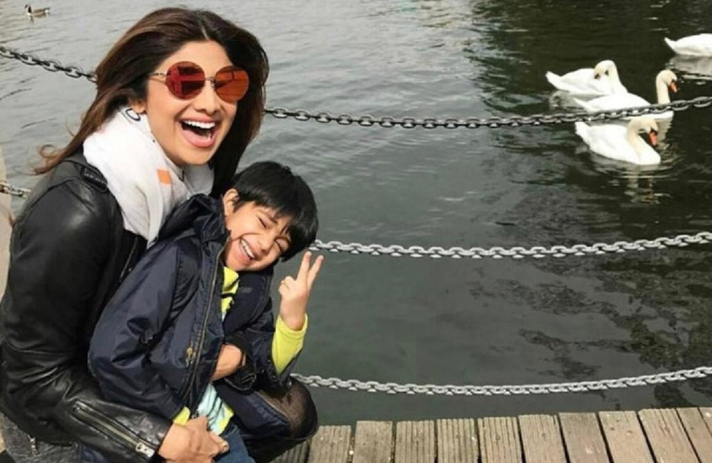 Shilpa Shetty's Diet Plan For Weight Loss. Shilpa sitting and laughing with her son near a river bank.