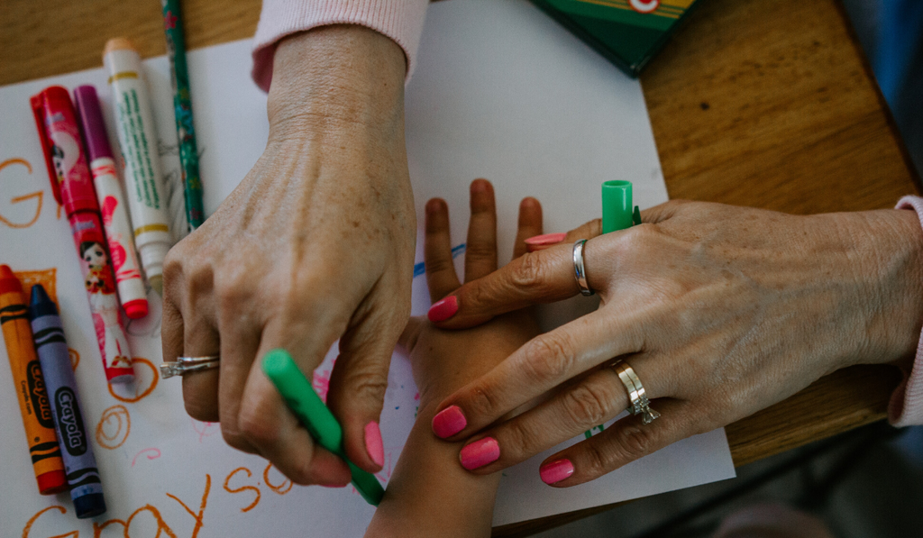 5 Drawing Games For Kids. A mothers hand drawing the hands of her kids with crayons.