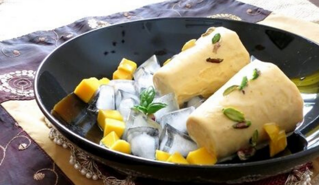 No-Fuss Mango Kulfi And Cheesecake Popsicle - Easy Dessert Recipes. Kulfi kept on a black plate with mango dressing.