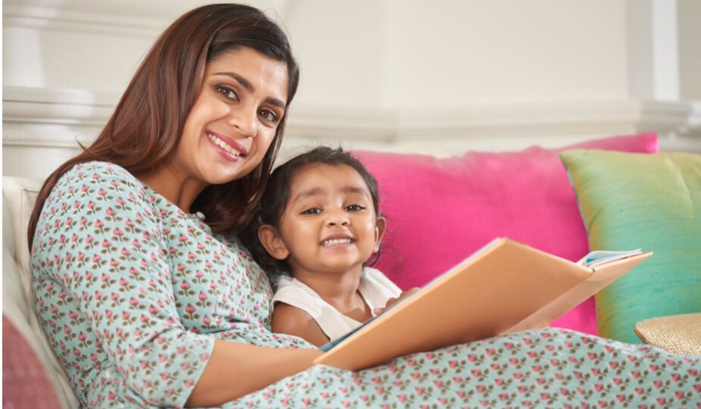 Books To Read By Children In Monsoon Season. Mother and Child smiling and enjoying a book.