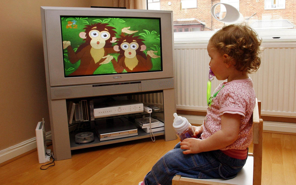 Steps To Screen-Free Mealtime. A girl enjoying the cartoon and holding the milk bottle.