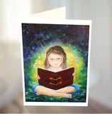 A young girl sitting with her legs crossed reading a large book in her lap. Watch the glow and luminescence coming from the book. By Australian artist Emma Harris and published as a greeting card by Cloud Publishing