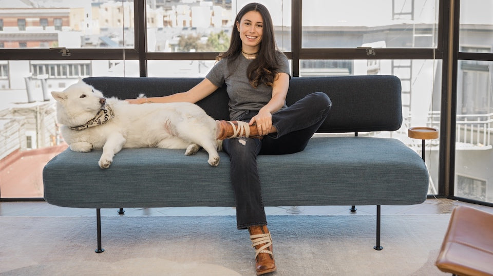 A woman with a dog on a couch