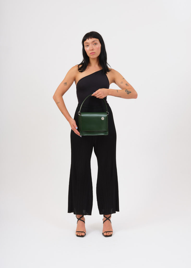 Model holding green pinch shoulder bag