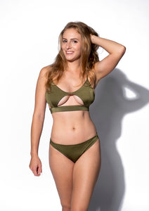 An olive green bikini top with a cutout in the lower centre to highlight lower cleavage above a band for support. Scoop neckline makes for a sleek silhouette.