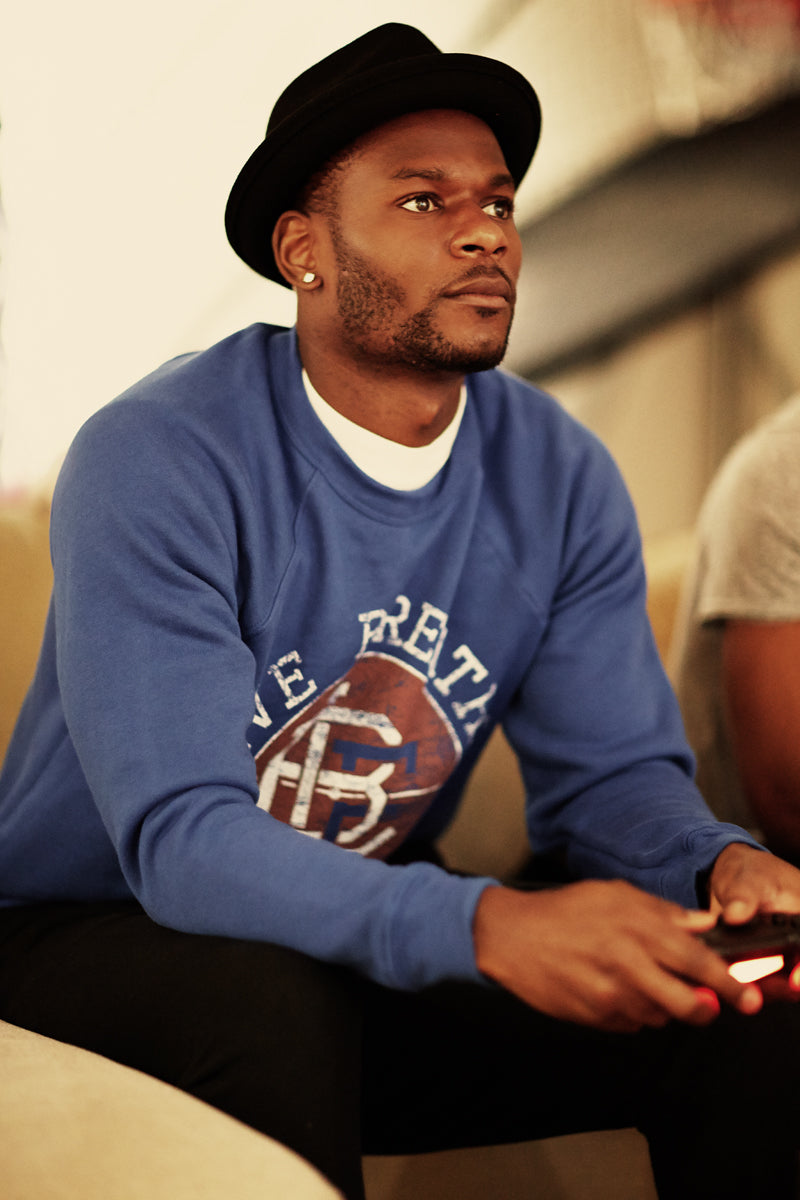 Maurice Edu wears Live Breathe Futbol Pitch Invaders sweater in royal blue