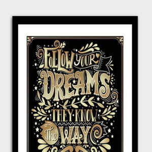 A framed poster with a black frame and the words follow your dreams, they know the way written in gold.