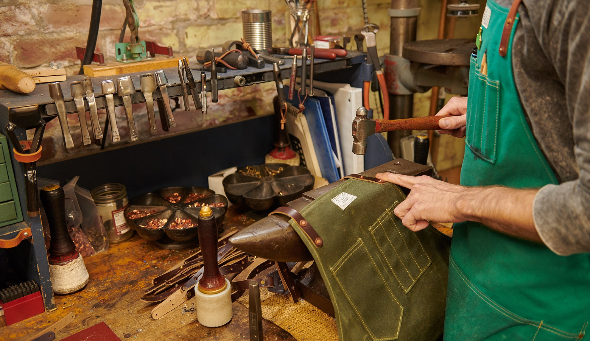Alec Hand Hammers Copper Apron Rivets In Artifact's Studio.