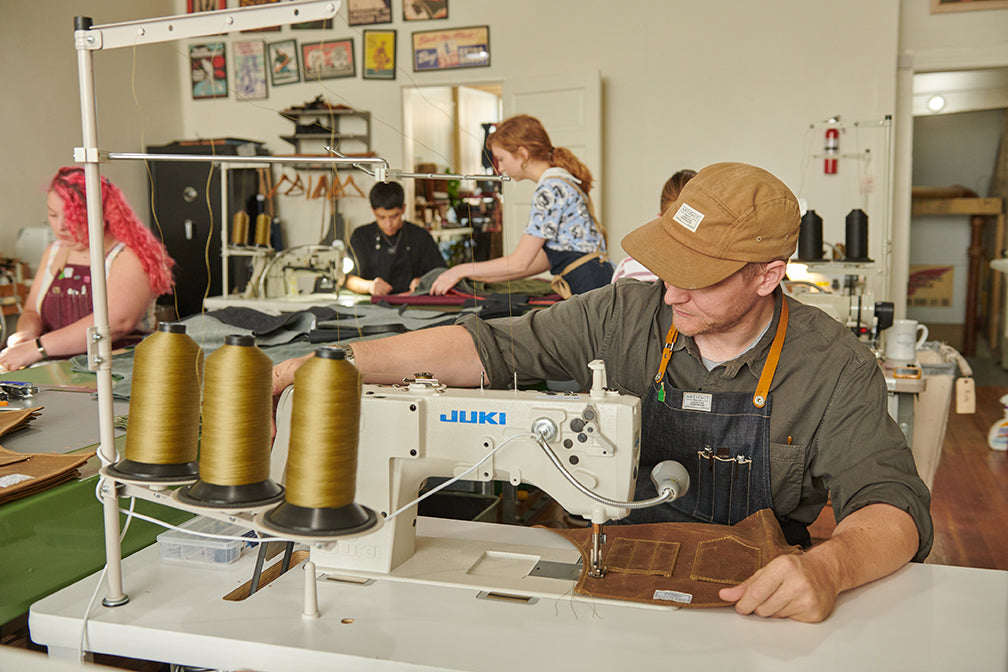 Founder Chris Hughes Sewing Aprons In Artifact's Omaha Studio