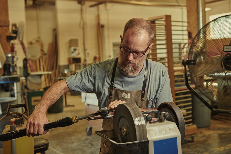 Todd McCollester in his Artifact Woodworking Apron Sharpening a Lathe Chisel on a Tormek T-8 Slow Speed Sharpener