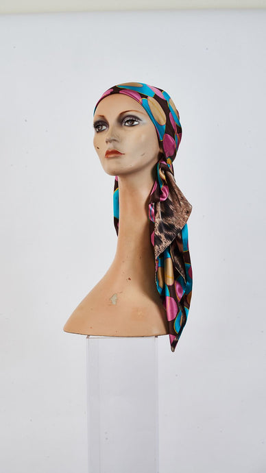 Printed circles and leopard silk carre tied around head
